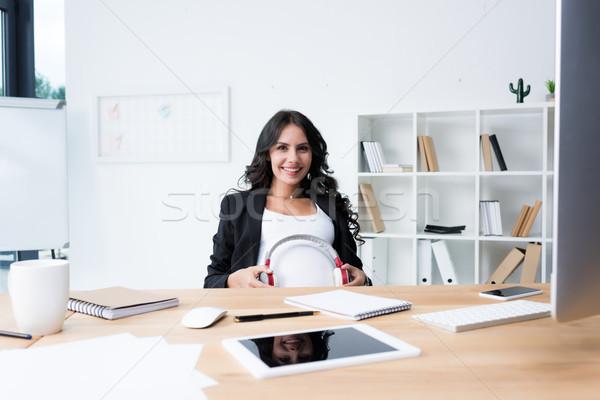 pregnant businesswoman with headphones on tummy Stock photo © LightFieldStudios