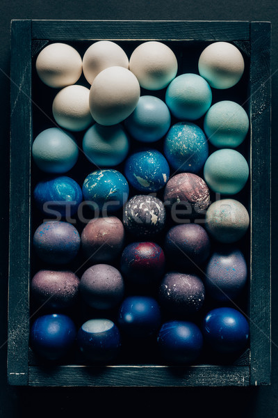 top view of colored painted easter eggs in wooden box on dark surface Stock photo © LightFieldStudios