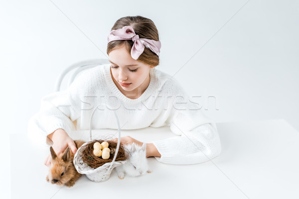 Cute bambina guardando coniglio basket easter eggs Foto d'archivio © LightFieldStudios