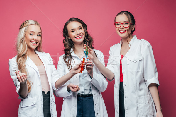 portrait of cheerful three doctors holding test tubes on pink Stock photo © LightFieldStudios
