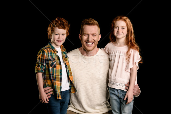 father with adorable redhead children hugging and looking at camera isolated on black Stock photo © LightFieldStudios