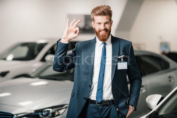 salesman in suit showing ok sign and looking at camera in dealership salon   Stock photo © LightFieldStudios