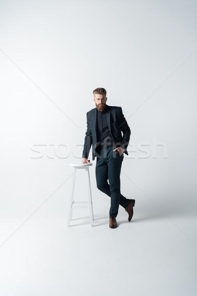 Elegante barbudo homem terno posando cadeira Foto stock © LightFieldStudios