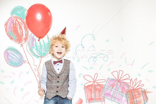 boy in cone hat with balloons Stock photo © LightFieldStudios