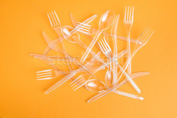 top view of set of various plastic cutlery isolated on orange Stock photo © LightFieldStudios