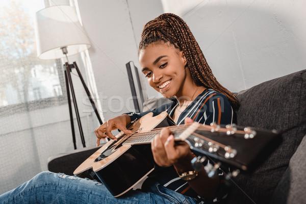 Zdjęcia stock: Kobieta · gry · gitara · kanapie · posiedzenia
