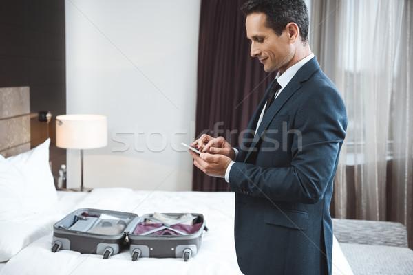 Zakenman telefoon hotelkamer formeel pak smartphone Stockfoto © LightFieldStudios