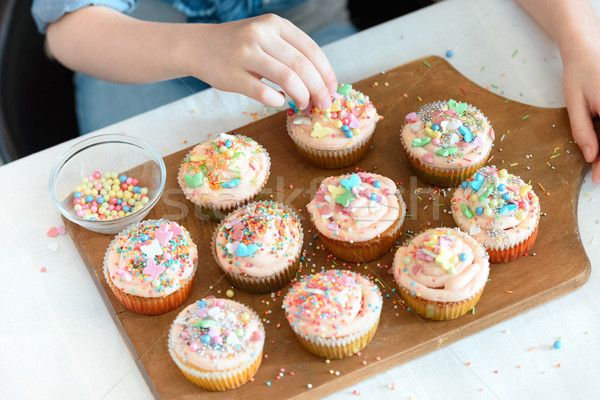 high angle view of girl decorating cupcakes on board with confetti  Stock photo © LightFieldStudios