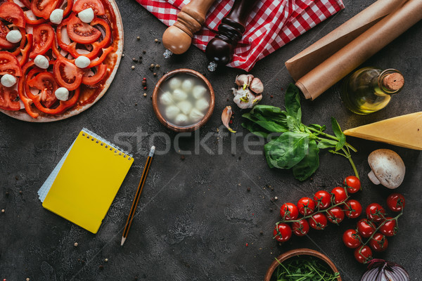 top view of uncooked pizza with notebook for recipe on concrete table Stock photo © LightFieldStudios
