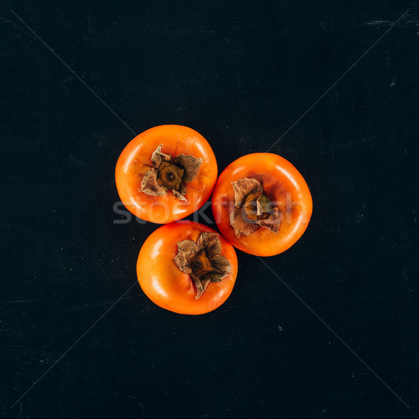 top view of three persimmons isolated on black Stock photo © LightFieldStudios