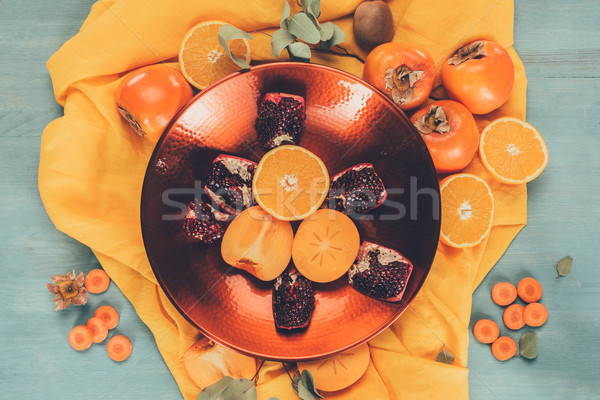 top view of persimmons with oranges and pomegranates on plate on orange tablecloth Stock photo © LightFieldStudios