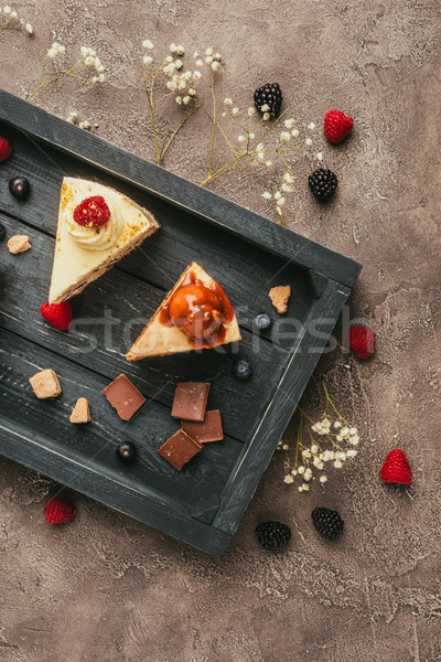 top view of sweet tasty cakes with chocolate and berries on wooden tray Stock photo © LightFieldStudios