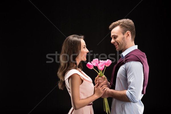 side view of smiling man presenting tulips bouquet to woman on black, international womens day conce Stock photo © LightFieldStudios