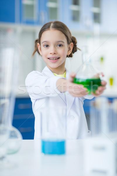 Kislány tudós tart flaska mosolyog kamera Stock fotó © LightFieldStudios