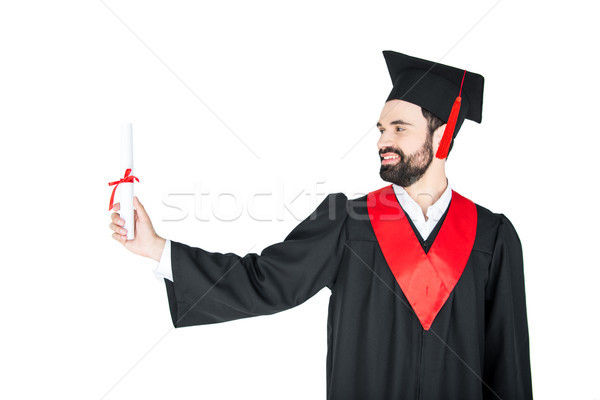 Happy young man in graduation gown holding diploma Stock photo © LightFieldStudios