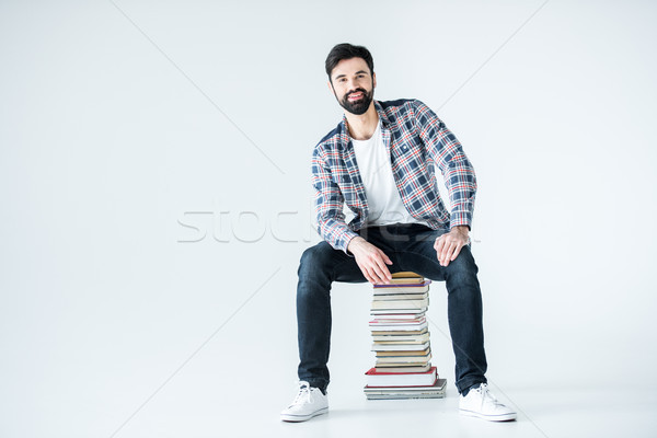 Barbu étudiant séance livres blanche Photo stock © LightFieldStudios