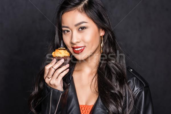 Stock photo: woman holding halloween cupcake