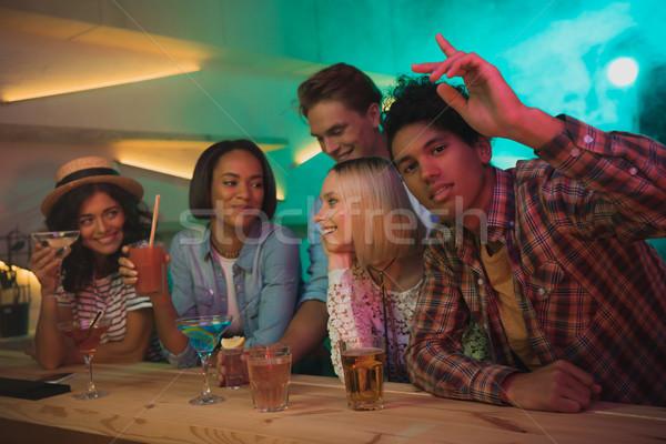 Több nemzetiségű barátok koktélok bár fiatalember gesztikulál Stock fotó © LightFieldStudios