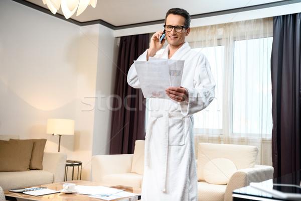 Businessman in bathrobe talking on phone Stock photo © LightFieldStudios