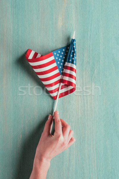 partial view of woman holding american flag in hand on blue wooden tabletop, presidents day concept Stock photo © LightFieldStudios