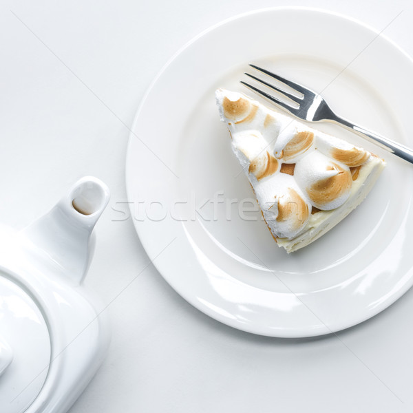 top view of delicious piece of cake with meringue and teapot on white table Stock photo © LightFieldStudios