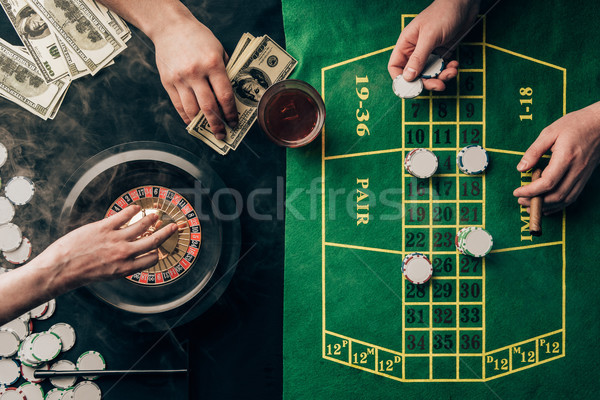 People placing bets while playing roulette on casino table Stock photo © LightFieldStudios