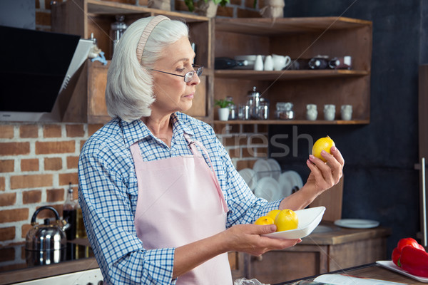 Femme regarder citrons cuisine supérieurs lunettes Photo stock © LightFieldStudios