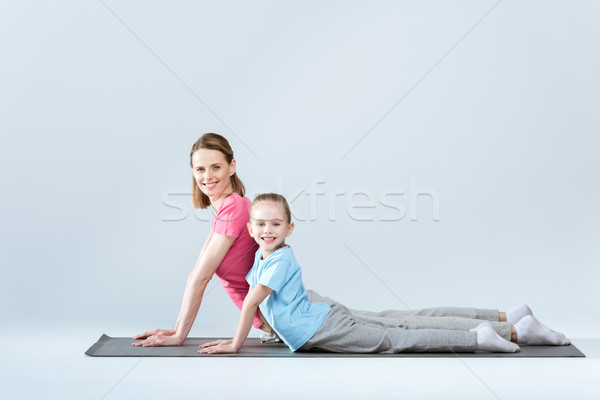 Side view of smiling sporty mother and daughter practicing upward facing dog yoga pose on white Stock photo © LightFieldStudios