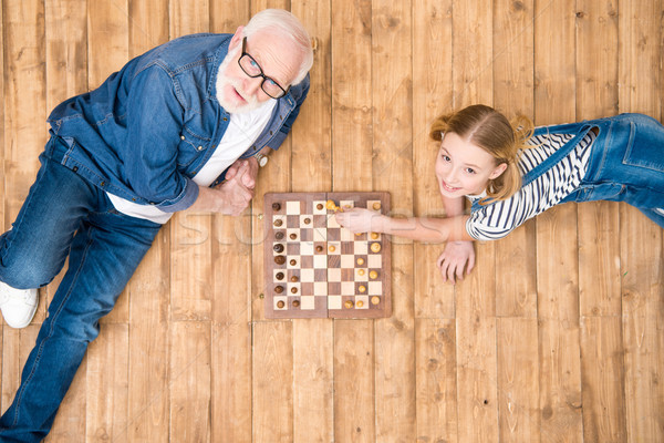 High angle view of smiling girl with senior man playing chess on wooden floor Stock photo © LightFieldStudios