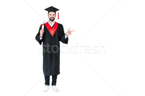 Full length view of happy young student holding diploma and pointing away with finger  Stock photo © LightFieldStudios
