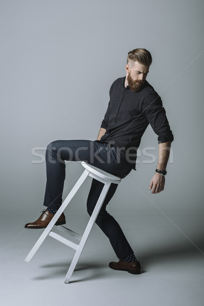 stylish bearded man posing on chair on grey Stock photo © LightFieldStudios