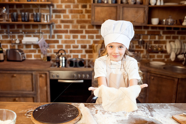 Stock photo: little girl making pizza dough on wooden tabletop in kitchen