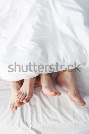 Stock photo: female feet stretching out of blanket