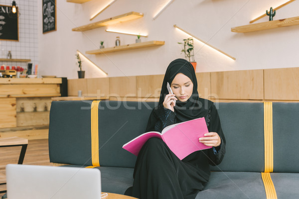 muslim woman reading magazine in cafe Stock photo © LightFieldStudios