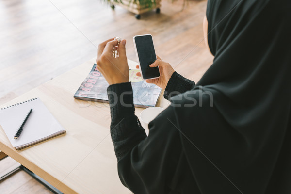 muslim woman using smartphone Stock photo © LightFieldStudios