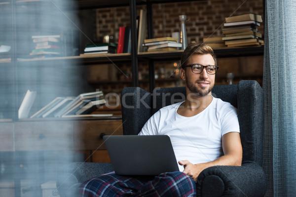 Człowiek fotel za pomocą laptopa uśmiechnięty młody człowiek domu Zdjęcia stock © LightFieldStudios