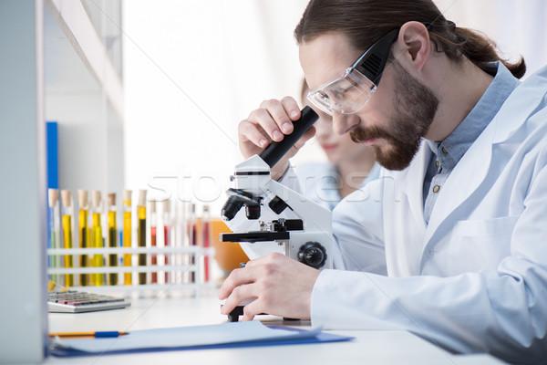Hombre mirando microscopio joven químico gafas Foto stock © LightFieldStudios