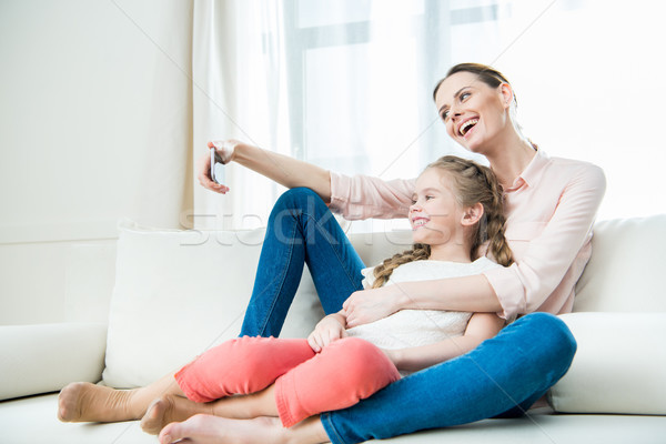 side view of happy mother and daughter sitting on sofa and making selfie Stock photo © LightFieldStudios