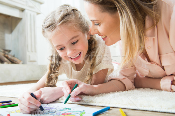 portrait of happy daughter drawing with mother at home Stock photo © LightFieldStudios