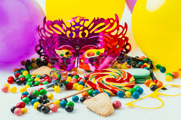 Stock photo: close up view of balloons, masquerade masks and candies, purim holiday concept