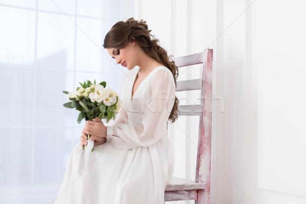 beautiful elegant bride sitting on big chair with wedding bouquet Stock photo © LightFieldStudios