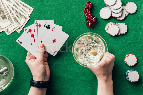Woman with alcohol in glass playing poker game by casino table Stock photo © LightFieldStudios
