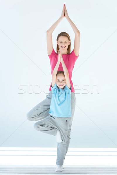 Smiling sporty mother and daughter practicing tree yoga pose and namaste mudra together on white Stock photo © LightFieldStudios