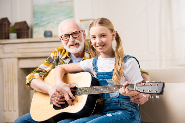 Happy grandfather and granddaughter sitting on sofa with guitar and smiling at camera  Stock photo © LightFieldStudios