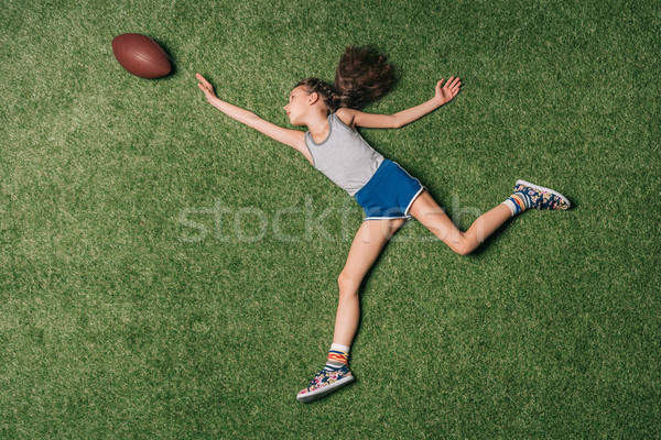 top view of little sportive girl catching rugby ball on grass, athletics children concept Stock photo © LightFieldStudios