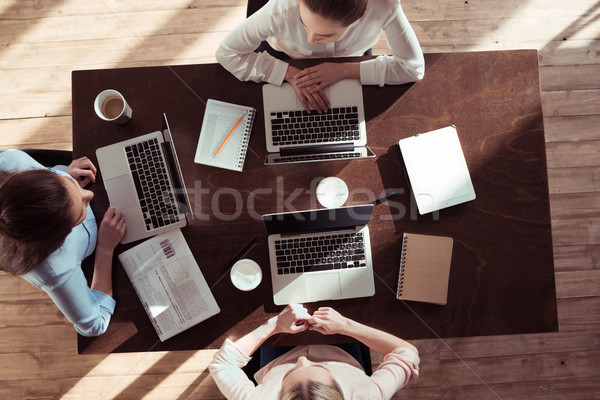 overhead view of businesswomen working at table on new business project Stock photo © LightFieldStudios