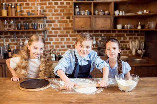 children making pizza dough on wooden tabletop in kitchen  Stock photo © LightFieldStudios