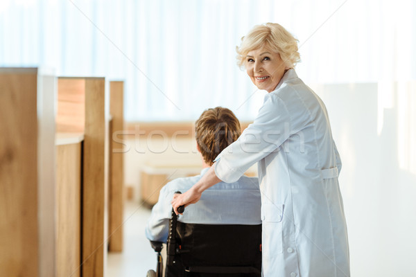 doctor rolling wheelchair with patient Stock photo © LightFieldStudios