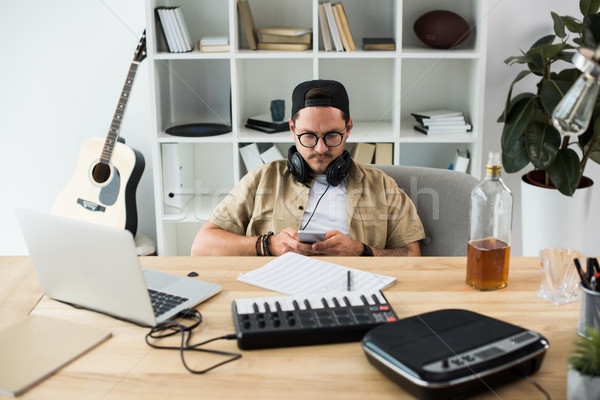 musician using smartphone at workplace Stock photo © LightFieldStudios