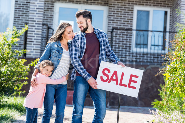 Stock photo: family standing in front of house on sale